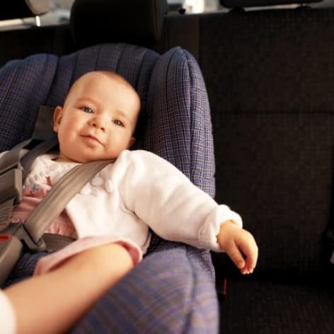 baby wearing white shirt sitting in car seat inside car with left hand hanging over seat