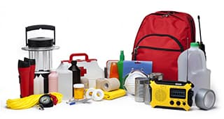various emergency items lined up such as, radio, first aid, lantern, water jug, batteries, gauze, etc. on a white background