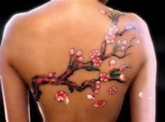 colored magnolia branch tattoo on a women's back