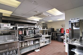 inside the kitchen/prep area of a retail restaurant with stainless steel equipment