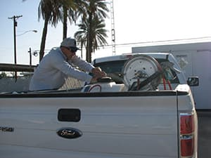 Public health vector control employee wearing a cap and grey jacket operating machinery on the back of white truck.