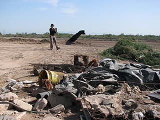 illegal dumping of trash in an open field with a public health environmental specialist takes a photo to document incident