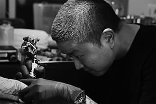 black and white photo with close up of tattoo artist performing his work