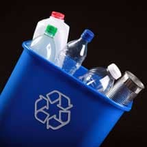 close up photo of small recycling trash can with an assortment of plastic bottles