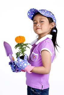 young girl wearing pink gardening shirt and jeans holding a pink trovel and orange flower,