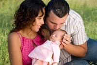 Man and woman couple holding a small baby girl in a pink dress, the family is sitting down in a field of grass.