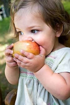 close up of a young child biting into a red apple